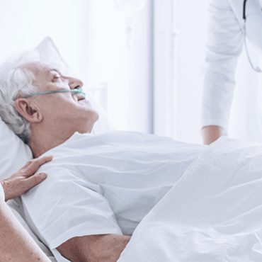 Doctor and family member supporting dying senior man lying in bed at hospital.
